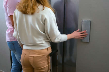 Hand of woman pressing the button of elewator and waiting it, back view. Female hand pushing the button of lift in hotel or business office, public place.
