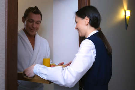 Young woman hotel worker maid in uniform is carrying a breakfast tray to the guests room. She is walking on corridor and giving a tray to man in bathrobe. The concept of room service in the hotel.