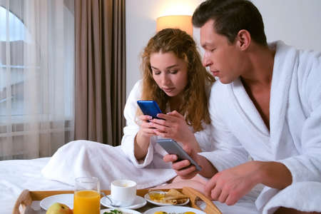 Man and woman are having breakfast in hotel room and reading news in their smartphones talking each other. Young family couple on vacations together. Luxury resting concept. Standard-Bild