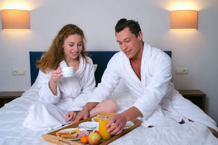 Man brought the breakfast tray to the hotel room and placed it on the bed next to the woman. Couple starting to eat breakfast together. Young family on vacation resting in their room.