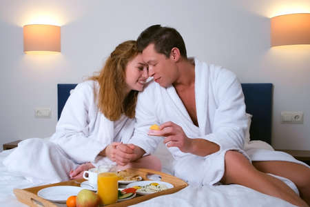 Family on vacations resting in their room. Happy young couple in bathrobes having a breakfast together sitting in bed in hotel. Man and woman are eating and drinking tea. She is feeding him.