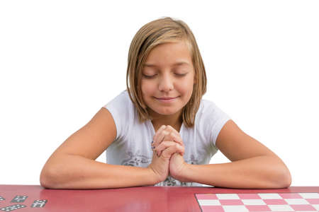 worship white: Young cute child girl pray at red desk in sunday school praying an having devotional