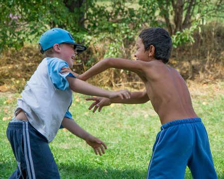 niño sin camisa: Racismo llevar a los niños a luchar chico gitano oscura contra chico blanco