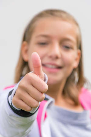 gesticulating: Young girl gesticulating thumbs up in front of face out of focus