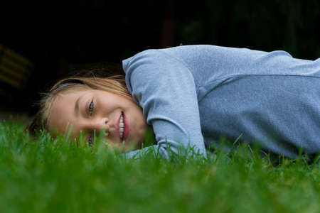 lays: Young child girl lays aside in grass smiling with open mouth