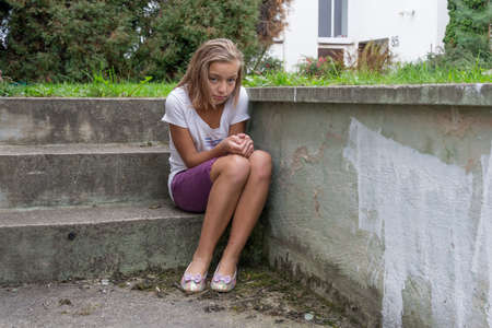 fear child: Bullied girl left alone cry sad on stairs without help Stock Photo