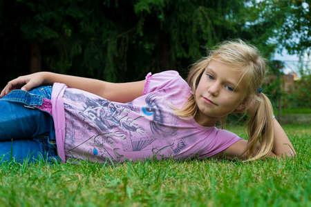 blonde yeux bleus: Jeune fille portant dans l'herbe pendant portrait d'été