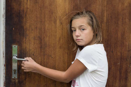 go inside: Young gypsy girl opening door of poor home scared to go inside afraid of domestic violence in divorced family Stock Photo