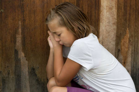 oppressed: Sad poor child weeping because has no friends in front of old wooden door