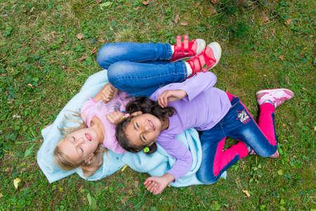 niños discapacitados: Dos niños con discapacidad mental yacían en una manta azul en la hierba en el jardín juntos