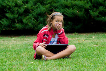 internet porn: Surprised and amused child with laptop hiding her mouth by hand Stock Photo