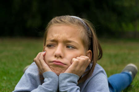 Sad and angry child girl lay in grass alone, nobody play with her without friends Stock Photo