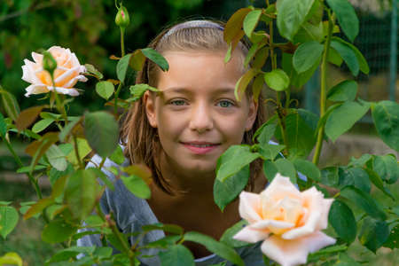 gypsy: Girl smiling between roses, gypsy child in flower garden