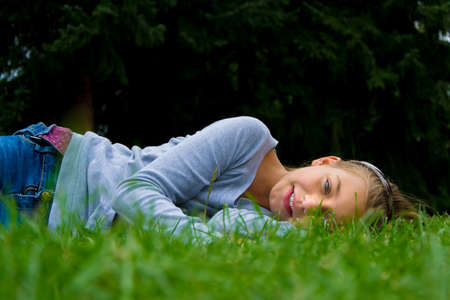 happines: Happy cute child girl lay aside in grass smiling having fun and expressing joy Stock Photo