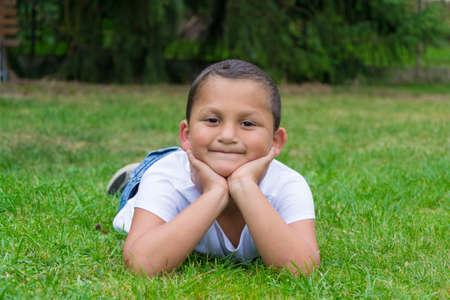 gypsy: Happy little gypsy child boy lay in grass smiling