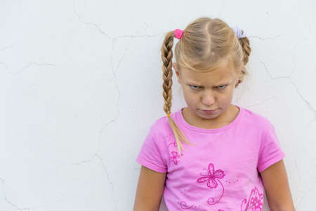disobedient child: Angry bullied child stay in front of white wall with annoyed expression Stock Photo