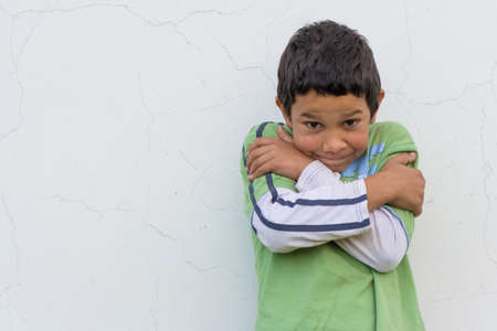 insecure: Shy insecure gypsy boy child with afraid expression stay in front of white cracked wall Stock Photo