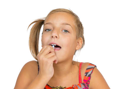 prescribed: Girl child going to swallow pill medicine, isolated on white background Stock Photo