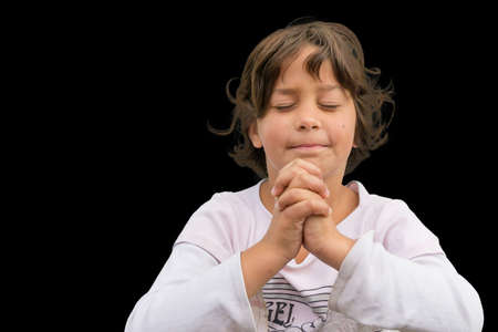 devotional: Small gypsy child praying with folded hands having devotional time, isolated on black background Stock Photo
