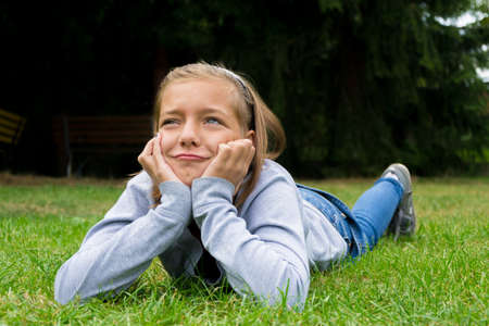 envious: Dissatisfied angry child girl lays in grass alone and unhappy
