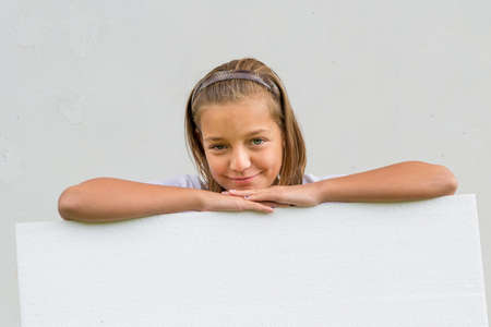 lean over: Cute smiling child girl lean over empty white paper sheet banner