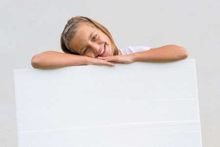 lean over: Smiling happy cute child girl lean heands and head over blank banner holging it and presenting as empty sheet Stock Photo