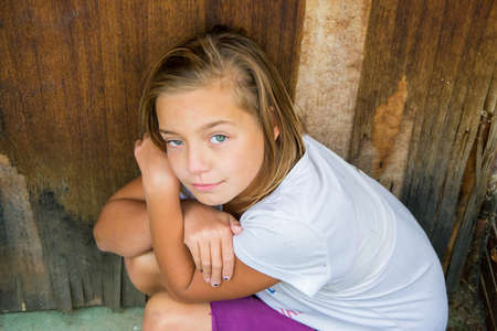 victim: Sad child girl victim of bullying violence or abuse sitting unhappy and alone looking directly up Stock Photo