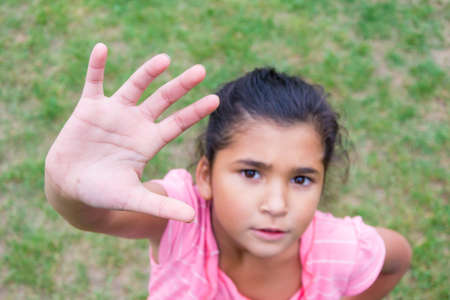 uncertain: Little child girl offering high five with curious and uncertain expression on face Stock Photo