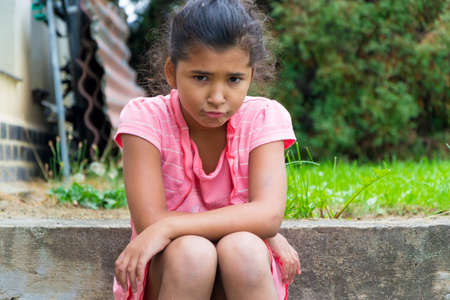 unaccepted: Angry and sad child girl sitting with upset expression on outdoor stairs Stock Photo