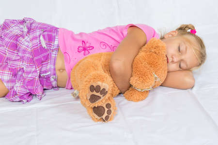 button: Young child girl sleeping with her toy teddy bear on white background