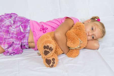 ombligo: Resto de la chica Niño triste y un abrazo del oso de peluche que pone en el fondo blanco Foto de archivo