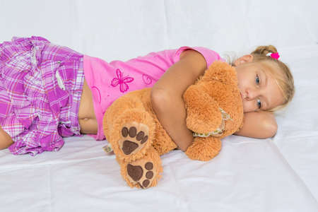 Sad child girl rest and hug teddy bear laying on white background