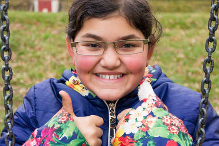 happines: Child girl wears glasses and show thumbs up beeing happy Stock Photo