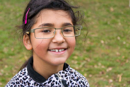 happines: Funny happy smiling child girl wear too big glasses for fun