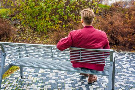 バレンタインの悲しい、一人で座って、公園のベンチで屋外の彼のガール フレンドを待っている日に若い十代の少年 写真素材