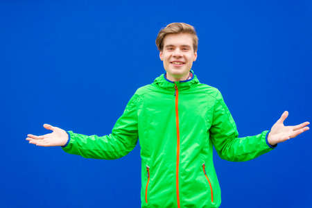 Very happy teenager boy gesticulating in good mood to express acceptance, invitation and positive approach is open to optimistic options with smile posing over contrast background