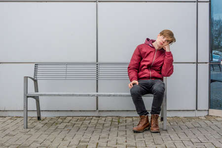 Bored teen waiting for parents outdoor on the metal bench in front of shopping center in city sitting alone thinking and hoping expressing dissatisfied emotions Stock Photo