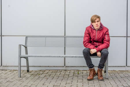 Teenager boy sitting on metal bench outdoor in city over urban gray background waiting