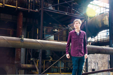 ironworks: Teen boy in heavy industrial area of ironworks