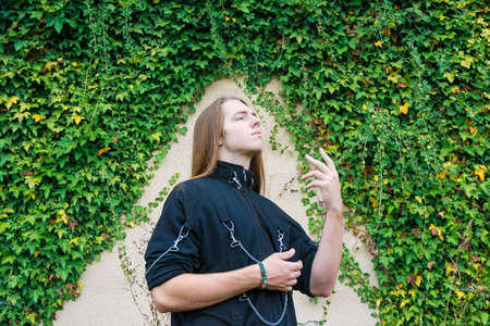 Rebelious teenager in metalist costume thoughtful over ivy wall