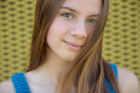 穏やかな表情と彼女の顔に長い髪の 10 代の少女の肖像画