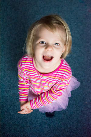Excited little child girl expressing joy and happy play; looking up on dark background 写真素材