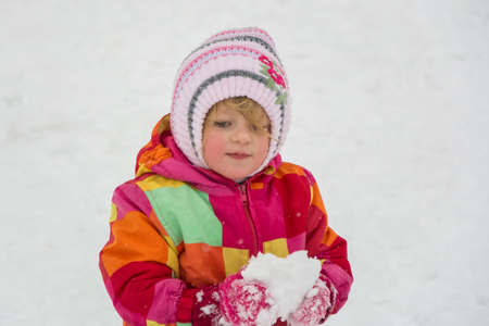 Little child holding snow in winter