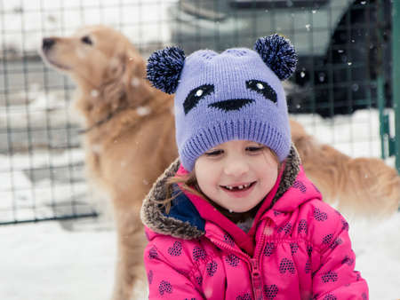 Cute child girl smiling outside in winter snow with dog 写真素材