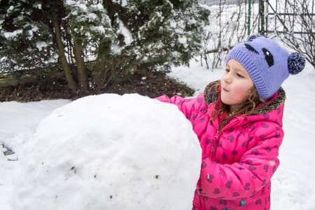 Little child girl in pink building snowman in winter