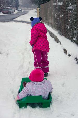 Little girl pulling her sister on snow slide in outdoor winter street