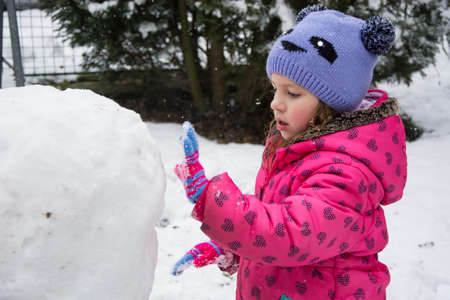 Child girl building snow ball for snowman