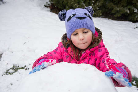 Little child building huge snowball for snowman in winter outdoor 写真素材