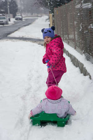 Child girl pulling her sister on snow slide on the street playing outside