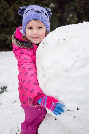 Little child girl hugs snowman in winter play 写真素材